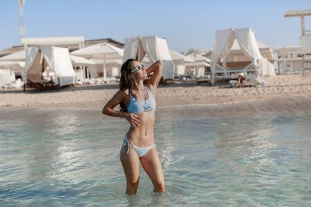Woman in swimsuit bikini standing knee-deep in the sea in the tourist resort.