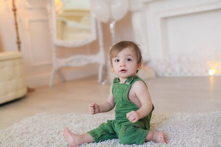 Boy 1 year sitting on the carpet in a bright room.