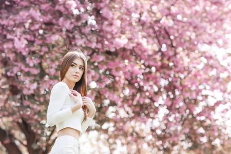Alone beautiful girl with a romantic hairstyle and a professional make-up enjoys a smell of pink colors in a garden. The girl dreams. A portrait of the beautiful girl model in the spring in the park