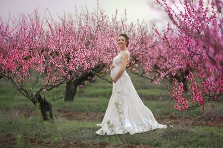 A woman in a wedding dress in a spring garden with trees at the moment of flowering.