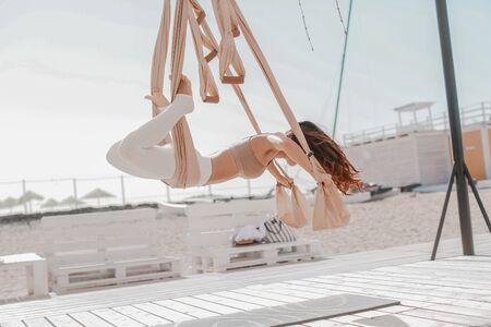 Woman on the beach in sportswear doing sports on hanging hammocks.
