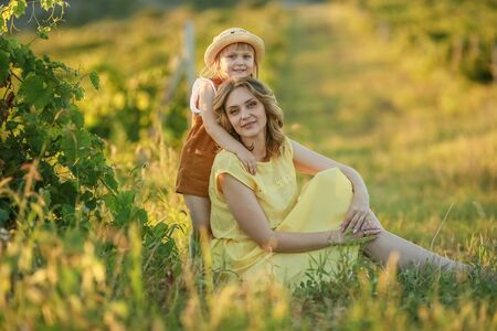 Mother is a grown woman hugging a child in a boundless green field.