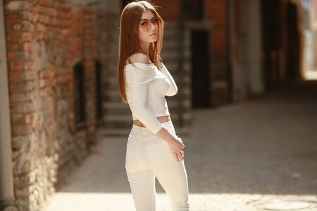 A female model in tight womens pants turns over her shoulder and looks at the camera. Фото со стока