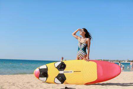 Beautiful woman on a sandy beach in sunglasses on background of ocean. Фото со стока