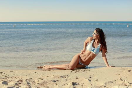 Girl in bikini and glasses on the ocean during vacation Фото со стока