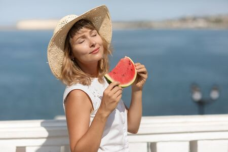A woman in summer in a white blouse with a slice of watermelon in her hands.