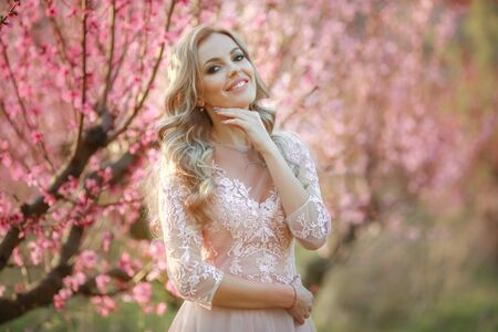Woman bride on wedding day alone in long pink dress in blossoming garden.