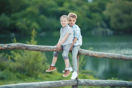 Two Boys Stand near Wooden Fence in Bavaria, Germany, Europe 版權商用圖片