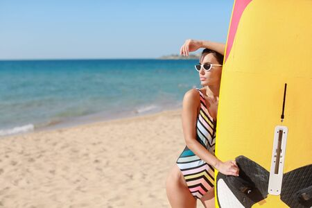 A surf athlete in a sports swimsuit and sunglasses on a sandy beach.