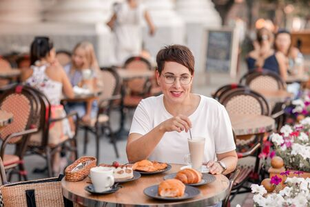 Woman stirs milkshake at table. European woman with short hair in Paris drinks hot drinks and eats croissants