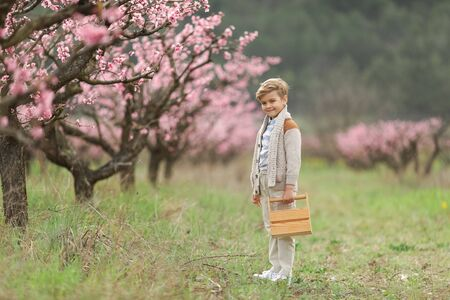 A kid in a park with a wooden suitcase. Cheerful cute boy first grader in pants with suspenders walks in the spring garden