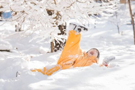 The boy fell into the snow and screams. Child winter in in cold weather happy and runs around on snow drifts