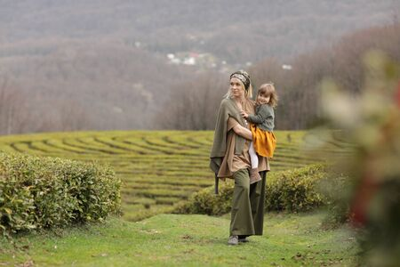 Mom with baby on tea plantation. A farmer woman walks with her daughter in a field with green plants