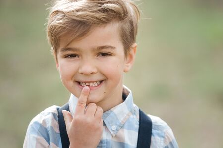 Boy, 6 years old, reveals a fallen tooth. The boy lost his first baby tooth and he demonstrates it on the street