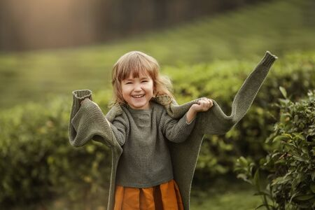 Baby girl in warm clothes in the field with tea tree plants Фото со стока