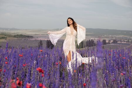 A woman whirls and dances in a field with lavender. Bride in white dress in lilac field with lavender