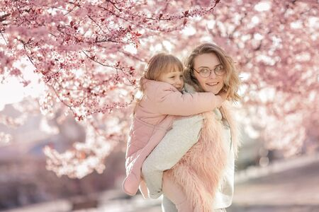 Mom hugs baby on walk in garden. Family mother and daughter among trees with flowers in blossoming period Фото со стока
