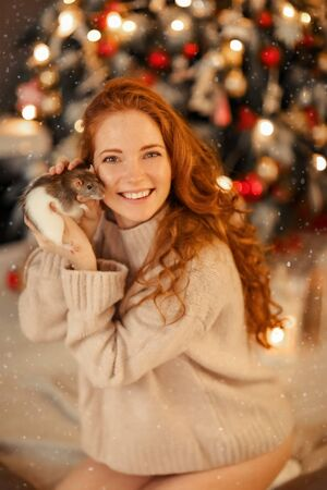 A woman with a rat in her hand sits near a Christmas tree Фото со стока