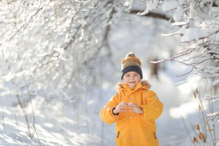 A child holds a heart-shaped hand. Child winter in in cold weather happy and runs around on snow drifts