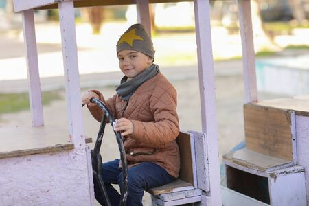 A child plays in the playground. a boy sits in a toy wooden car on the Playground