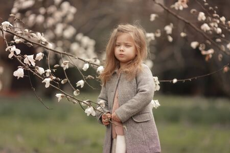 A child in the background of blossoming white trees.