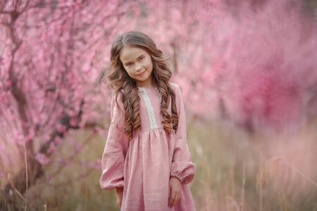 A girl with curly hair in the park. Girl in pink dress in a blooming garden with pink trees Stok Fotoğraf