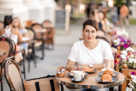 A woman dines in a street cafe. Lesbian woman with short male haircut eats croissants for Breakfast in a restaurant on the street
