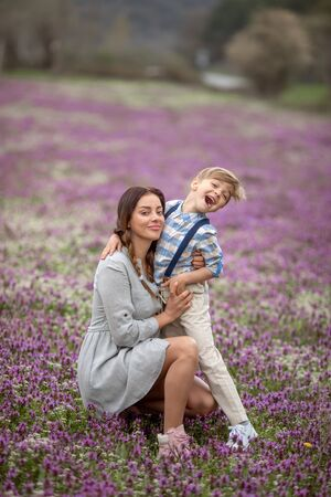 Mom tickles son. A family of two a mother and son of a child walk through a young lavender field Фото со стока