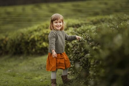 Baby girl in warm clothes in the field with tea tree plants.