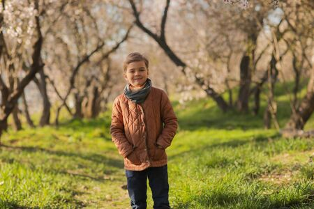 A boy of 7 years in early spring in nature walks along the path directly to the camera Фото со стока