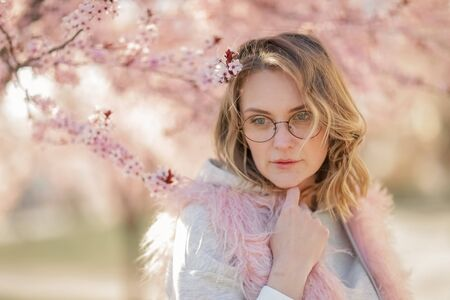 Portrait of a blonde woman against a backdrop of pink flowers. Portrait of female model near pink peach blossom tree
