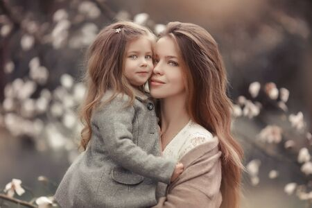 Portrait of a mother with a baby against the background of blossoming white trees. Фото со стока
