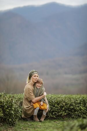 A woman with a child walking on a tea plantation.