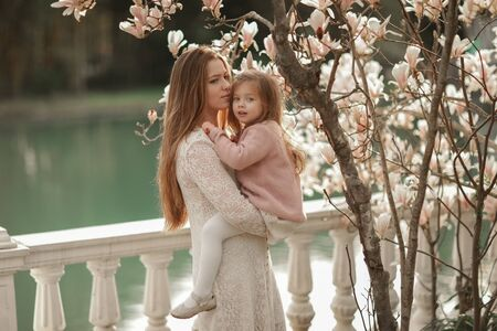 A woman with a daughter in the park. Mom hugs and cuddles her beloved daughter to her chest during a walk