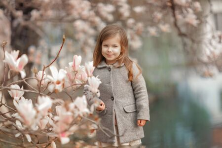 A child near the flowers of the mognolia. A girl looks into the camera and walks in the park against the background of the lake