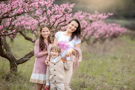 Young Beautiful Mother at Spring, Pink Blooming Tree at the Background.