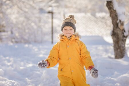 Boy dressed in warm bright clothes in winter. Child winter in in cold weather happy and runs around on snow drifts