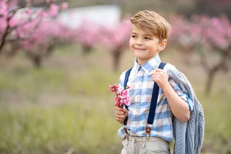 A boy with a bouquet of flowers in his hands looks thoughtfully into the distance. Child 6-7 years in pants and shirt holding a twig with fruit flowers