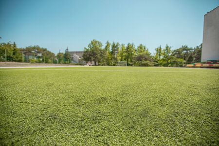 Lawn on a football field at a low angle. Soccer ball close up on green grass at extreme point
