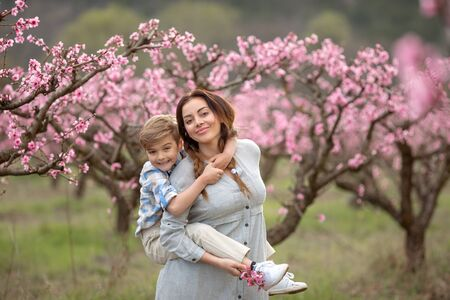 The baby and his mom in the park. The mother carries the child on her back and the child laughs and has fun
