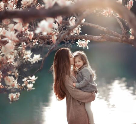 Unrecognizable girl with a child in the background of a lake and a tree. A woman with a daughter in the park.