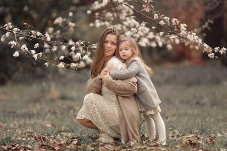 Baby hugs mom amid white blossoming trees. Фото со стока