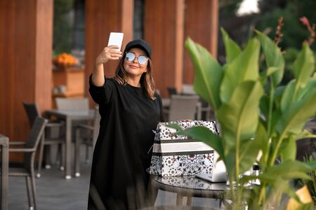 Woman takes a selfie on her phone dressed in traditional Islamic clothes. Standard-Bild