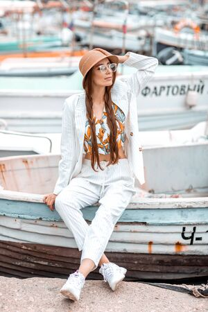 A young girl in a white suit sits on the stern of a pleasure boat. Standard-Bild