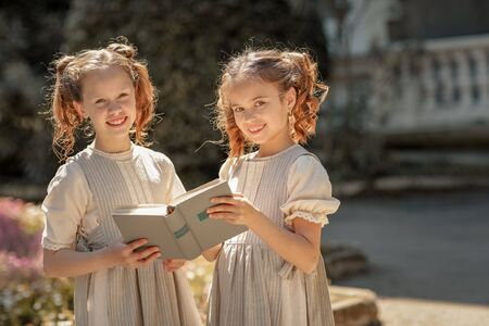 Two girls of primary school schoolgirls read a book in the courtyard of the academy. Standard-Bild
