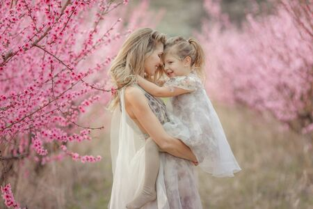 Mom and daughter dressed in dresses. Mom holds and hugs daughter touching each others foreheads Standard-Bild