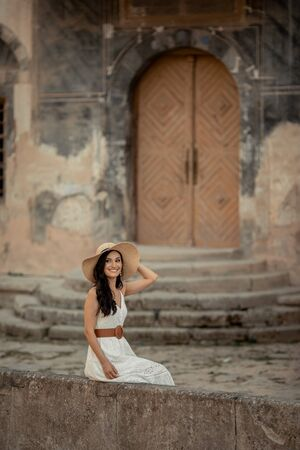 Beautiful woman of eastern appearance among ancient street stone architecture.