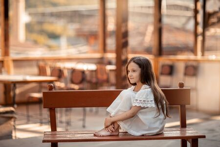 A child with bare feet sits on a wooden bench