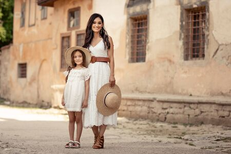 Young beautiful mother of eastern appearance walks with her daughter on the ancient streets of the Mediterranean city.