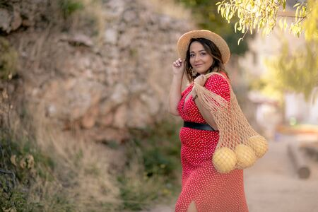 Sweet woman with a basket of fruit. Woman carries ripe fruit in shopping bag